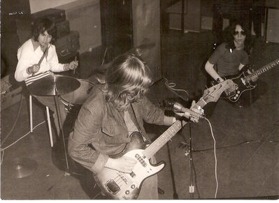 Rehearsing in the school music room, circa 1973. Jon Easton in the foreground, Paul on the drums, and myself in shades literally getting down to play a high lick. Click to enlarge